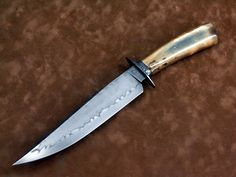 Don Hanson, MS- W2 fighter with a vivid clay hardened hamon. Strange Walrus ivory handle with blue peaking out of a few spots from the center. Solid 18K rose gold pin.
