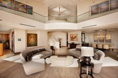 Ultra modern two story open space features glass-railing balconies overlooking twin semi-circle sofas with circular beige ottoman at center.