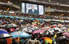 South Africans brave the rain as they listen to U.S. President Barack Obama speak during a memorial service for Nelson Mandela at FNB Stadium in Johannesburg, South Africa December 10, 2013. REUTERS/Kevin Lamarque