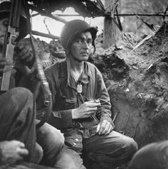 American Captain Byron E. Bradford in a trench during the fight against Japanese forces holding the area.