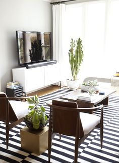 Fabulous living room with soft gray paint color and flatscreen TV on modern white media cabinet as well as Harmon Kardon Sound Bar System. Living room features mid-century modern chairs and West Elm Raw Edge Coffee Table over black and white striped rug, Ikea Stockholm Rug