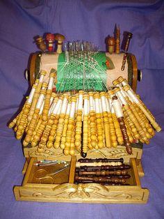 bobbin lace pillow mounted on a stand with drawers to hold extra bobbins