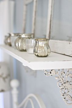 shelf over bed with candles on it