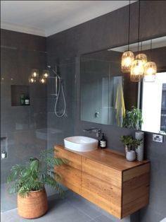 Timber vanity unit in a dark tiled bathroom