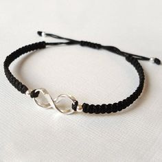 Classic Friendship bracelet with a central Infinity charm.This pretty Friendship bracelet is made from strong black cord and features a central Infinity charm in a lovely flat ribbon design giving it a fluid effect and framed with 2 sterling silver bead Bracelet Crafts, Macrame Bracelets, Handmade Bracelets, Jewelry Bracelets, Black Bracelets, Cute Jewelry, Beaded Jewelry, Diy Leather Bracelet, Armband Diy