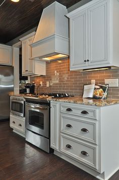 Traditional Kitchen with Custom hood, Flat panel cabinets, Complex granite counters, Subway Tile, One-wall