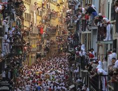 Pedro Armestre—AFP/Getty Images July People standing on balconies look at participants as they run in front of Alcurrucen's bulls during the first bull run of the San Fermin Festival in Pamplona, northern Spain. San Fermin Pamplona, Art Actuel, Running Of The Bulls, Pictures Of The Week, Places To See, Cool Photos, Amazing Pictures, Beautiful Places, Amazing Places