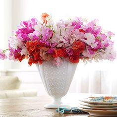 Delicate, fragrant sweet peas look particularly pretty when arranged in a lacy-patterned milk-glass vase for a table scape