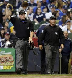 Umpire Ted Barrett, left, signals an out call after listening to the central replay booth in New York in the sixth inning of an opening day baseball game between the Atlanta Braves and Milwaukee Brewers, Monday, March 31, 2014, in Milwaukee. An umpire's call has been overturned for the first time under Major League Baseball's expanded replay system, with Brewers' Ryan Braun ruled out instead of safe.