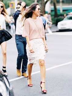 Aimee Song of Song of Style in a lace skirt, open-knit sweater, and red ankle-strap sandals