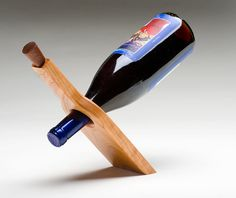 Handmade wooden wine holder defies the law of gravity. Wine holder made from cherry with a mahogany cork. Wine holder makes a great gift for any