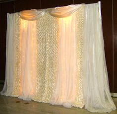 DIY Wedding Backdrops Ideas | This backdrop is designed with floral fabric, shear panels and lights ...