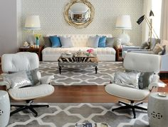 Contemporary living room features accent wall clad in Imperial Trellis wallpaper adorned with gold twigs mirror over white tufted armless sofa dressed in gray, turquoise and blue velvet pillows flanked by low end table topped with gray table lamps with turquoise trimmed lamp shades.