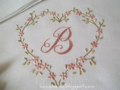 Expertly Embroidered Monogram encircled with delicate pink flowers and heart.