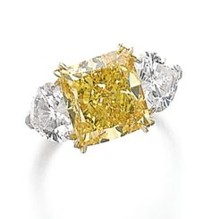 FANCY VIVID YELLOW DIAMOND RING, RONALD ABRAM The cushion-shaped fancy vivid yellow diamond weighing 5.06 carats, set between heart-shaped diamond shoulders weighing 1.02 and 1.04 carats respectively, signed Ronald Abram.
