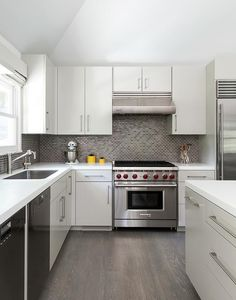 White and gray kitchen features white flat front cabinets paired with white quartz countertops and a gray mini brick tile backsplash alongside a gray wash oak wood floor.