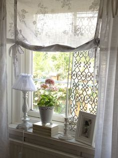 Roman sheer shades for the front windows with curtain on rings to go across the whole window wall.