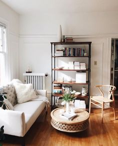 Cute small living room with bookcase, white couch, round West Elm coffee table #smallspaces