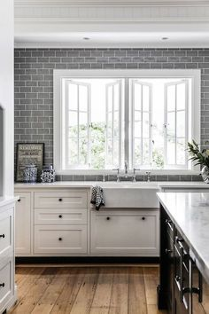 Grey subway tile is a stunning backdrop for white or marble look countertops in this kitchen design.