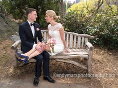 a bride and groom, just married in Central Park, on a rustic bench