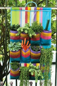 Make a hidden water reservoir for pots in the garden.When you pot up your flowers dangle a few 'wicks' (mop strings) out of the drainage holes. The wicks should be placed a few inches into the potting mix in your planter.  Great idea for patio herb garden and love the organizers colors!