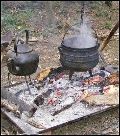 a cast iron pot over a fire and a kettle for camp cooking