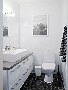 Peili, allaskaappi, wc istuin, lattia laatoitus, seinät maalaus, valo peilin yhteyteen