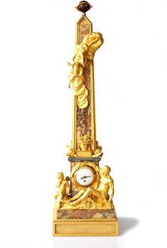 Exceptionnelle pendule Louis XVI à forme d'obélisque, vers 1770. Photo Accademia Fine Art    Réalisé en bronze doré finement ciselé et brocatelle de Sienne. Elle est rehaussée d'une figure d'Iris et à sa base d'un personnage barbu, d'un amour et de quatre dauphins.