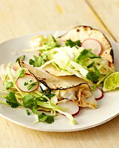 Grilled Fish Tacos: Protein-packed halibut gets a flavor boost from cabbage, radishes, cilantro, and scallions in these tacos full of taste and texture.