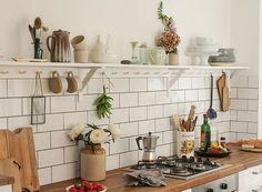 A cozinha toda branquinha ganha o colorido dos alimentos. A prateleira é uma ótima opção para colocar vasos e itens do dia a dia, além de ter um suporte para pendurar outras coisas (Foto: Divulgação/Laura Pashby)