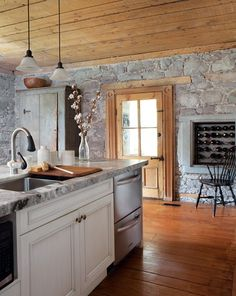 Beautifully restored stone walls hearken back to a simpler era. The original tamarack ceiling and pine door of this kitchen highlight this Quebec home's rich history, while stainless steel appliances and contemporary fixtures offer modern style and functionality.