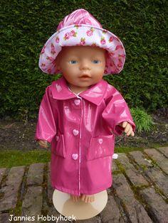 Regenjasje en -hoedje van roze lakstof, afgezet met katoen met rozenprint. Voor BabyBorn 43 cm. Patroon Christel Dekker.