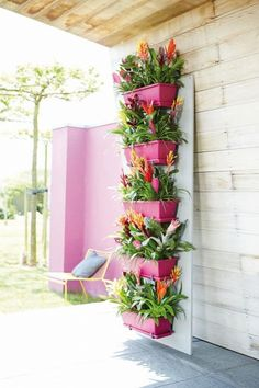 a nice way to brighten up your balcony - brightly painted flower pots placed vertically on a wall