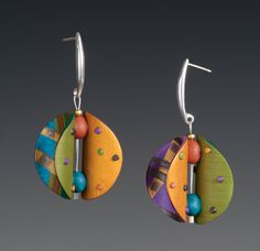 Wings Round Multi-Color Earrings by Arden Bardol. Handcrafted polymer clay forms the body of this piece. Each earring is formed by back-to-back, rounded circular shapes with polymer spacers separating the wings. Colorful dots adorn the interior of each wing. Each earring within the set is one of a kind. The earring finding is sterling silver. Each piece is lightweight and is approximately 2 inches long.