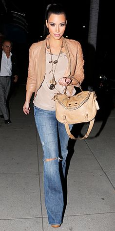 Strolling in Beverly Hills in flared jeans and a tan leather jacket.   If it were me, I would wear the jeans in a darker color and without the hole for a more polished look.