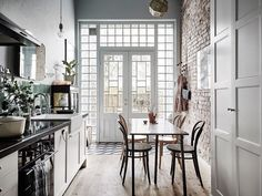 Boho bistrostyle Scandinavian kitchen with exposed brick wall, Thonet chairs