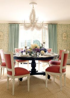 Dining room with white coral chandelier, glossy wood pedestal dining table, red French back dining chairs, diamond pattern wool rug, teal blue curtains window panels and ivory & teal wallpaper.