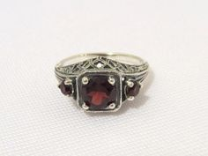 Vintage Art Deco Sterling silver Genuine Garnet Filigree Ring Size 6 on Etsy, $45.00  I could never find this type of thing in my size.  :( I really like how the sides look like gothic window tracery.