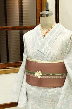 細やかな絣風の模様が形作るタイルのような格子模様に凛とした気品ただよう水仙の花が染めだされた、さっぱりとした白の夏着物風の浴衣です。
