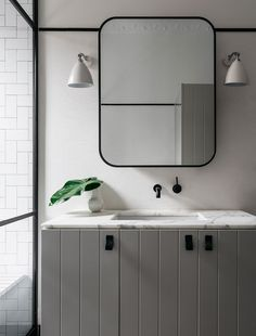 Contemporary yet classic bath with unique styling on the marble vanity top; wall mounted black faucet; black framed mirror