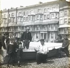 Fishermen and Children around a rowing boat on the Worthing beach. Marine Parade buildings in the background. Caps. ImageDate 	c1895