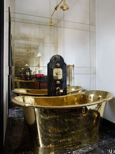 A guest bathroom's brass tub echoes the golden veins in the portoro-marble floor | archdigest.com