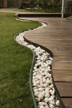 Use rocks to separate the grass from the deck, then bury rope lights in the rocks for lighting. Awesome for our back yard!!.