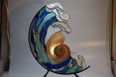This is a beautiful stained glass with Nautilus shell. My son made the stand.
