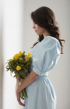 Portrait of happy young brunette woman holding a bouquet of yellow flowers.