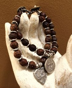 """A silver replica of an old Burmese coin is at the center of this bracelet of vintage Thai prayer beads and silver discs. Crocheted onto silver gore-tex thread, this 7"""" bracelet is fastened with an abalone button."""