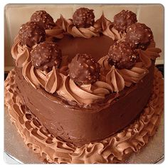 Chocolate orange heart shaped cake with chocolate orange buttercream. Decorated with piped milk chocolate buttercream and Ferrero rocher chocolates