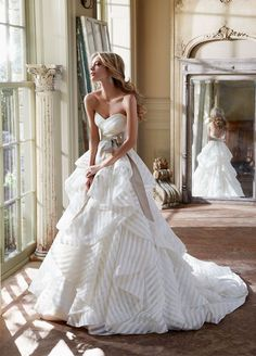 Ballgown wedding dress in striped ivory organza with strapless sweetheart neckline. Features low back, ruched bodice, and elaborate layered skirt with horsehair trim and chapel train.