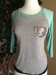 Play ball!  This baseball top is right on trend with minty sleeves.  Stylish sequined pocket makes for such a cute top.   Available on www.closetjewels.com