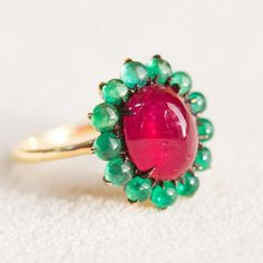 """""""5 carat unheated cabochon Burma ruby flanked with fine cabochon Colombian emeralds.  Nothing in this ring is treated; they're all natural stones set with…"""""""